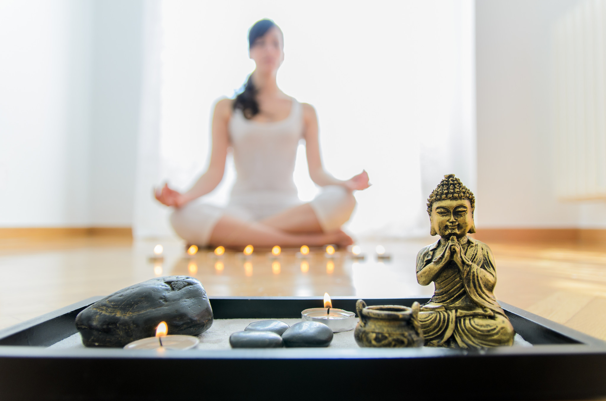 A small altar in the foreground with a figure of Buddha, candles, sand and stones. In the background, out of focus, the silhouette of a woman meditating in yoga posture, seated on the floor.
